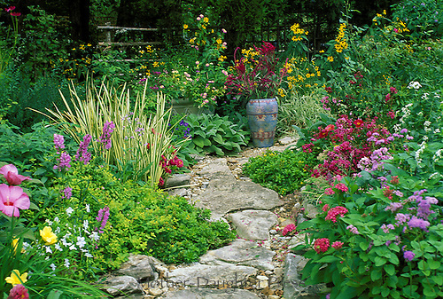 Stone path curves through blooming garden where a painted Mexican pot adds interet and color