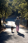 Woman walking with her dog down a country road, Auburn California