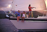 Woman and girls dancing hula as they sail into Hanalei Bay at sunset, North Shore, Kauai, Hawaii