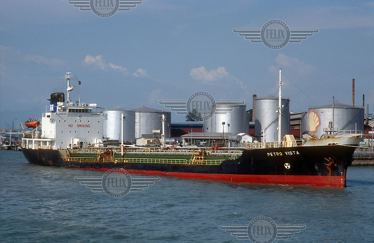 Ship docked by oil containers.