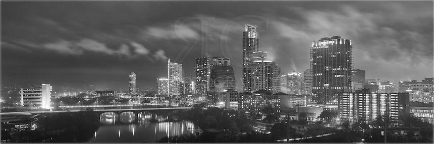 On a rainy, foggy evening over Austin, Texas, clouds sweep across the skyline and Ladybird Lake.