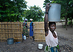 "Joyce Dzongololo carries water home from the village pump in Chidyamanga, a village in southern Malawi that has been hard hit by drought in recent years, leading to chronic food insecurity, especially during the ""hunger season,"" when farmers are waiting for the harvest."