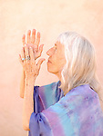 Photograph of a senior woman in devotional gesture.