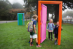 "Curious children wander around Chris Johanson's ""Door Sculpture to Talk About the Idea of Different Possibilities You May Have to Process Your Life."""