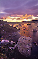 731000078 a stormy sunset casts a soft purple tint on boulder erratics and the sila river in northern canada near wager bay in the nunuvat territories