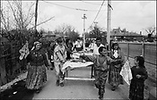 ROMANIAN ORTHODOX EASTER CELEBRATIONS. CARRYING TABLES OF FOOD, DRINK AND PRESENTS TO THE HOUSE OF GODPARENTS. SINTESTI, ROMANIA, EASTER 1995..©JEREMY SUTTON-HIBBERT 2000..TEL./FAX. +44-141-649-2912..TEL. +44-7831-138817.