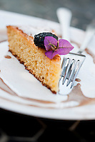 Close up of a piece of coconut cake served with a dried prune and garnished with a bougainvillea flower