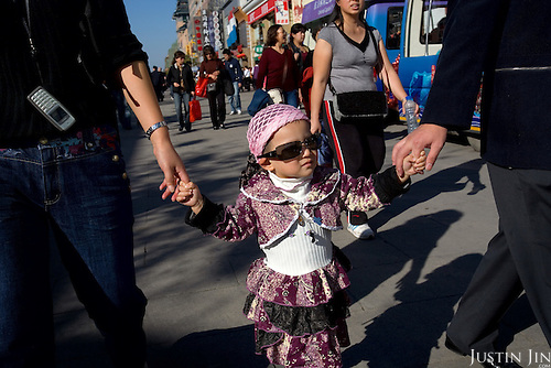 A Chinese girl walks with her parents on the Wang Fu Jing pedestrian street in Beijing, which is getting ready to host the 2008 Olympics.