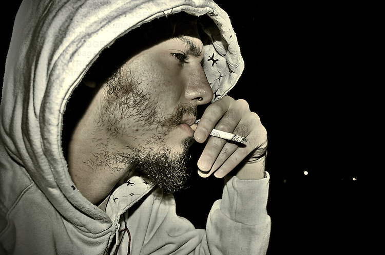 A young unshaven male smoking a cigarette wearing a hoody