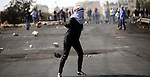 A female Palestinian protester uses a sling shot to throw stones at Israeli security forces during clashes with Israeli security forces near the Beit El settlement on the outskirts of Ramallah in the West Bank, on October 17, 2015. The unrest that has engulfed Jerusalem and the occupied West Bank, the most serious in years, has claimed the lives of 34 Palestinians and seven Israelis. The tension has been triggered in part by Palestinians' anger over what they see as increased Jewish encroachment on Jerusalem's al-Aqsa mosque compound. Photo by Shadi Hatem