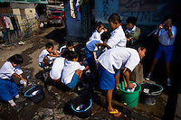 Kindergarten students at Kartini Emergency School collect water from a pump during a lesson in clothes' washing. Acquiring practical skills is an important part of the education programme. Since the early 1990s, twin sisters Sri Rosyati (known as Rossy) and Sri Irianingsih (known as Rian) have used their family inheritance to set up and run 64 schools in different parts of Indonesia, providing primary education combined with practical skills to some of the country's most deprived children.