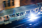 A CTA Green Line El train makes a few sparks as it passes through the Loop on a rainy night.