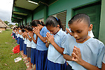 Mayan school children begin their morning with flag raising and a prayer in southern Belize