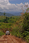 A 4 wheel drive on a dirt road in Kanchanaburi, Thailand, against a mountain and jungle background