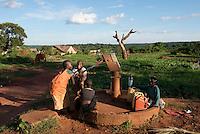 Children pumping water at the well. Kigulu town, Klobulenzi, Uganda, Africa