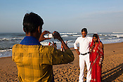 A newly wed couple seen taking a photo on Puri Beach along the Bay of Bengal in Puri, Orissa, India. A dip in its salty waters is believed to hold great religious significance, as a result these golden sand beaches sees is a never-ending rush of pilgrims and tourists. Photo: Sanjit Das/Panos