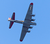 "The B-17 ""Flying Fortress"" bomber ""Nine-O-Nine"", tail number 231909, flying over Orange County, CA on May 12, 2013.  Taken about an hour before sunset, the bottom is clearly visible and evenly lit.  The vintage plane has been resored by The Collings Foundation to it's WWII (World War 2) configuration, after having served in nuclear bomb testing in the 1950's, being sold as scrap, and being converted into a forest-fire supression plane."
