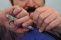 Claudio San&ograve;, artigiano del cuoio nel suo laboratorio mentre lavora un borsa a forma di pesce.<br /> Claudio San&ograve;, leather craftsman in his workshop, while he working a bag like a form of  big fish