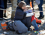 A refugee mother hugs her child on a beach near Molyvos, on the Greek island of Lesbos, on October 30, 2015, after they crossed the Aegean Sea from Turkey in a small overcrowded boat provided by Turkish traffickers to whom the refugees paid huge sums. They were received in Greece by local and international volunteers, then proceeded on their way toward western Europe.