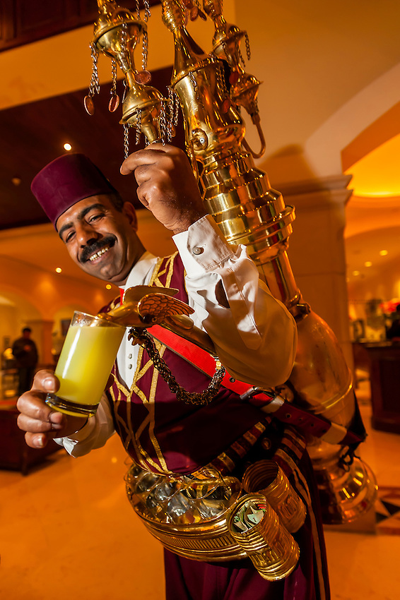 Man serving cups of lemon juice, Movenpick Resort & Spa Dead Sea, Sweimeh, at the Dead Sea, Jordan.
