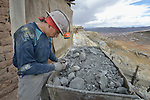 A miner inspects minerals in an ore wagon outside a mine in Potosi, Bolivia. The mine produces silver and other metals.