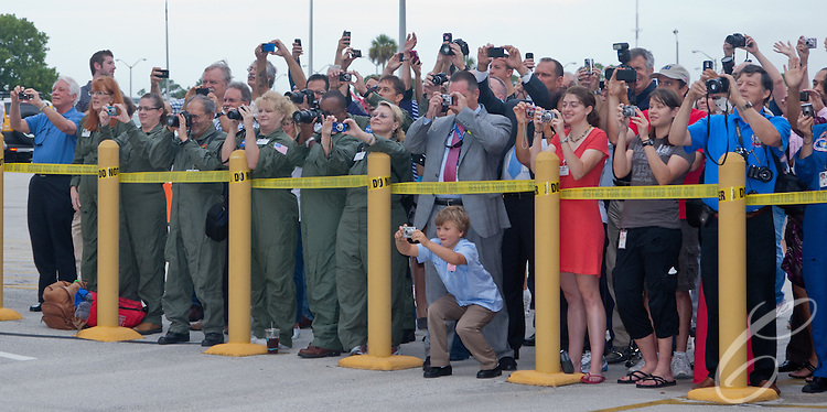 NASA employees and guests take pictures as the  crew of Space Shuttle Atlantis leaves for the launch pad at Kennedy Space Center on Friday, July 8, 2011.  Atlantis' mission is the final one of the program's 30 year history.