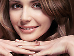 Closeup beauty portrait of a beautiful smiling young caucasian woman resting her chin on her hands
