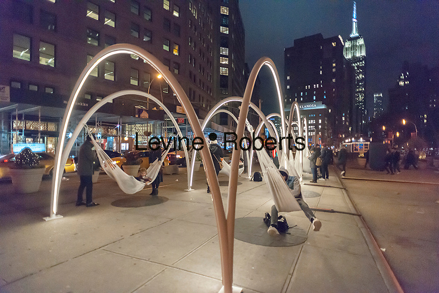 """Visitors to Flatiron Plaza in New York on Tuesday, November 22, 2016 interact with """"Flatiron Sky-Line"""" created by architectural firm LOT. The Christmas installation is the centerpiece of the Flatiron 23rd Street Partnership's  holiday programming. The ten illuminated arches with hammocks suspended underneath engage visitors to relax and to contemplate the architectural wonders of the neighborhood, specifically the Flatiron Building. (© Richard B. Levine)"""