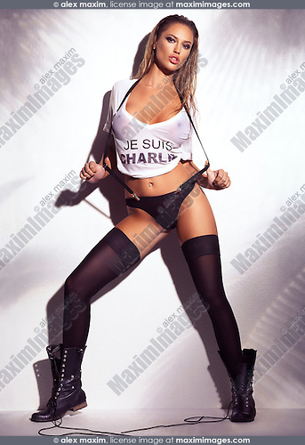 Sexy woman with wet blond hair wearing a wet Je Suis Charlie shirt, underwear and black stockings with boots on white background. Artistic glamour photo.