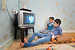 Abdul and Mohammed Al Saye, 8- and 11-year old refugees from Aleppo, Syria, watch television in their family's small apartment in Amman, Jordan. Their family received a box of household supplies from International Orthodox Christian Charities, a member of the ACT Alliance. IOCC supports Syrian refugee families in Jordan, who aren't allowed by the government to work, as well as many poor Jordanian families that have been negatively impacted by rising rents and prices for basic commodities, the result of the influx of Syrians into the country. <br /> <br /> Parental consent obtained.