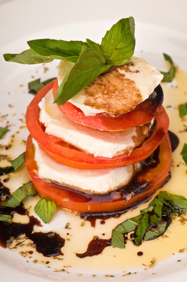 Salad of fresh mozzarella with vine-ripened tomatoes, pungent basil and extra virgin olive oil.