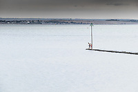 Children stand on the end of a breakwater in the Thames Estuary at Southend, Essex.
