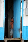 South America, Brazil, Amazon.  A young boy peers timidly from doorway of house on the Amazon River.