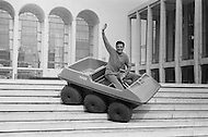 October 1966. French singer Gilbert Becaud waves as he drives an all-terrain vehicle down an exterior stairway in New York. Image by © JP Laffont