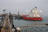 AL-BASRA OIL TERMINAL, IRAQ: A worker fishes while a tanker is loaded with crude at the Basra Oil Terminal..