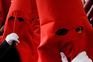 The Holy Week participants wearing a red tunic and a hood with the conical hat (capirote) walk down the street of Malaga, Spain, 5 April 2007.