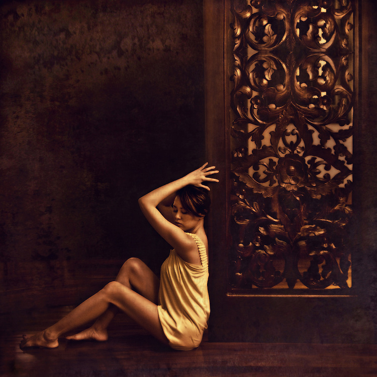 A young asian woman wearing a short yellow dress leaning against a decorative wooden screen