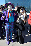 Manhattan, New York City, New York, USA. October 10, 2015. Cosplayers, The Joker in purple and Lady in black carrying white mask, are outside in front of the Javits Center during the 10th Annual New York Comic Con. NYCC 2015 is expected to be the biggest one ever, with over 160,000 attending during the 4 day ReedPOP event, from October 8 through Oct 11, in Manhattan
