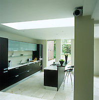 This contemporary kitchen extends into the back garden and is generously lit by a large central skylight