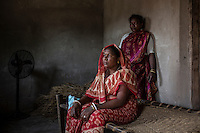 """Bhudni Tudu, 44 years old, comes from the village of Birbans. Three years ago her brother in law accused her of witchcraft, slowly managing to bring also Bhudni's son and husband on his side. Left alone by the rest of the villagers, one month ago she had to flee the village, after her son tried to kill her. Today, Bhudni is hosted by her sister (standing behind her), but she cannot cope with what happened to her. """"I don't have any hope for the future"""", she says. """"I just think of killing myself""""."""
