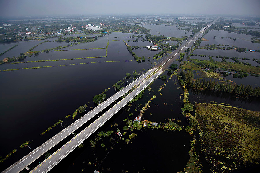 Floods cover a part of highway in outskirts of Bangkok October 20, 2011. Thai Prime Minister Yingluck Shinawatra defended her government's response to the country's worst floods in half a century on Wednesday as troops battled to protect industrial centres and Bangkok braced for rising waters.   REUTERS/Damir Sagolj (THAILAND)