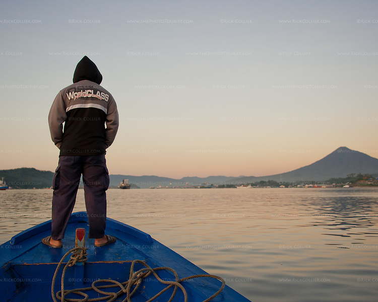 A crewman watches for small boats or other obstructions on the approach from Lembeh to Bitung, North Sulawesi, Indonesia.
