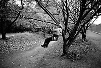 USA. New York. Central Park. An elderly man is doing pull up exercises on a tree's bough. He is carrying on his shoulder a bag from the New York Yankees which are a baseball team. Fitness session. A pull-up is a variety of upper-body compound pulling motions for the purpose of exercise. The most popular current meaning refers to a closed-chain bodyweight movement where the body is suspended by the arms, gripping something, and pulled up with muscular effort. As this happens, the wrists remain in neutral (straight, neither flexed or extended) position, the elbows flex and the shoulder adducts and/or extends to bring the elbows to or sometimes behind the torso. © 1985 Didier Ruef