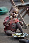 Displaced by war, a girl savors her meager portion of food in the Makpandu refugee camp in Southern Sudan, 44 km north of Yambio, where more that 4,000 people took refuge in late 2008 when the Lord's Resistance Army attacked their communities inside the Democratic Republic of the Congo. Attacks by the LRA inside Southern Sudan and in the neighboring DRC and Central African Republic have displaced tens of thousands of people, and many worry the attacks will increase as the government in Khartoum uses the LRA to destabilize Southern Sudan, where people are scheduled to vote on independence in January 2011. Catholic pastoral workers have accompanied the people of this camp from the beginning. NOTE: In July 2011 Southern Sudan became the independent country of South Sudan.