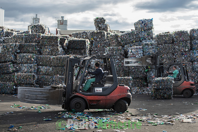 """An employee drives a forklift past stacks of plastic waste collected in the sea by fishermen at a plastic processing plant in Chiva, near Valencia on November 3, 2015. Ecoalf, a Spanish Madrid-based firm founded in 2010, has already launched """"a new generation"""" of clothes and accessories made from plastic bottles, old fishing nets and used tires found on land.   © Pedro ARMESTRE"""