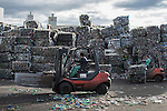 "An employee drives a forklift past stacks of plastic waste collected in the sea by fishermen at a plastic processing plant in Chiva, near Valencia on November 3, 2015. Ecoalf, a Spanish Madrid-based firm founded in 2010, has already launched ""a new generation"" of clothes and accessories made from plastic bottles, old fishing nets and used tires found on land.   © Pedro ARMESTRE"