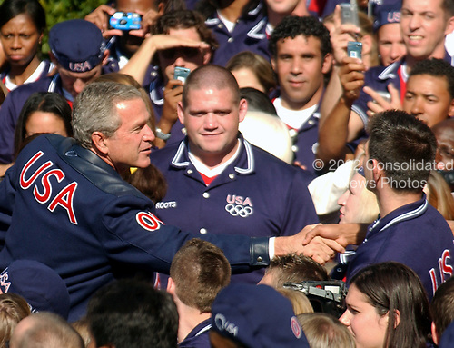 United States President George W. Bush shakes hands with members of the 2004 United States Olympic and Paralympic teams on the South Lawn of the White House in Washington, D.C. on October 18, 2004.  Olympian Rulon Gardner looks on.<br /> Credit: Ron Sachs / CNP