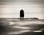 A woman wearing a red hat perched on the edge of the ocean.