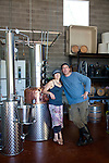 Stone Barn Brandyworks, a micro-distillery in SE Portland, Oregon run by Sebastian and Erica Degens.  They make products that include rye whiskey, pear brandy, and other varieties of distilled spirits and operate out of a very small, green warehouse space.  Their products are not yet for sale other than directly from them.  Sebastian and Erica Degens by their copper still.
