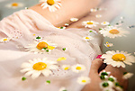 Girl in dress with daisies floating around her legs and dress.